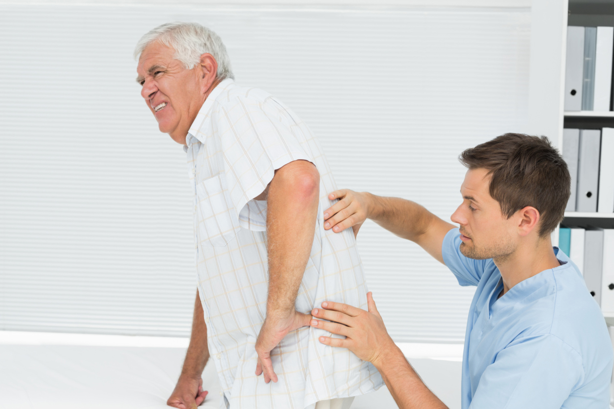 Male physiotherapist examining senior mans back